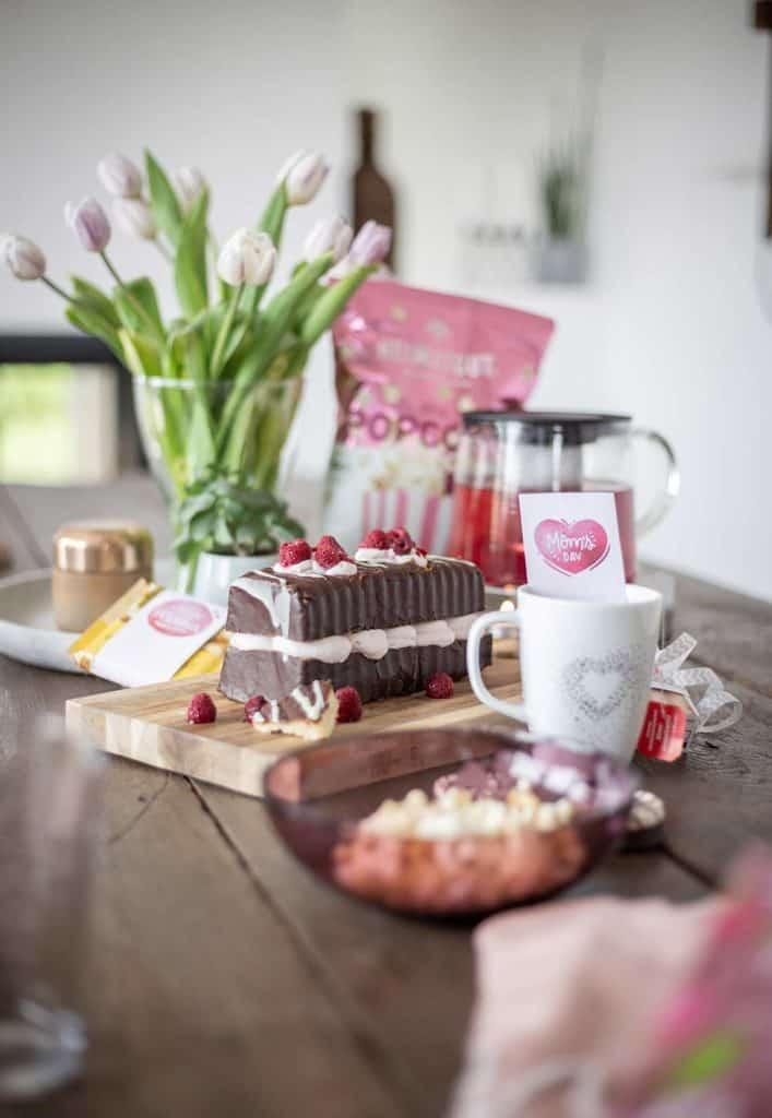 Kaffetisch mit Kuchen und Blumen zum Muttertag